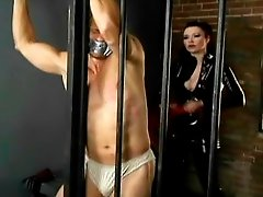 Dangerously hot mistress in black latex overall whips male slave and clamps his nipples